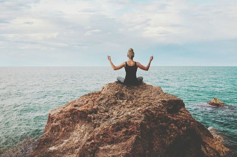 Full length of woman exercising on rock in sea against sky