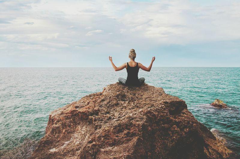 Full length of woman on rock in sea against sky