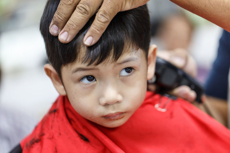 Cropped hand cutting boy hair