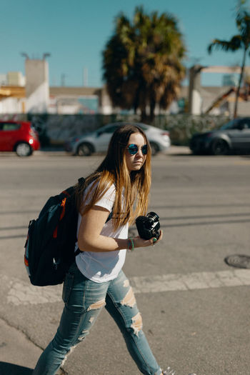 Young woman wearing sunglasses on road in city