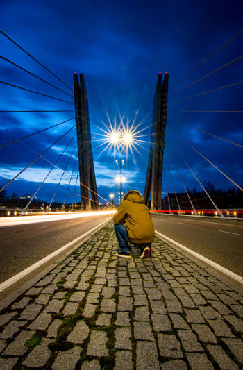 Rear view of man sitting on bridge against sky at night