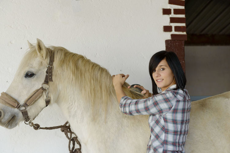 Portrait of smiling young woman combing horse hair while standing against wall