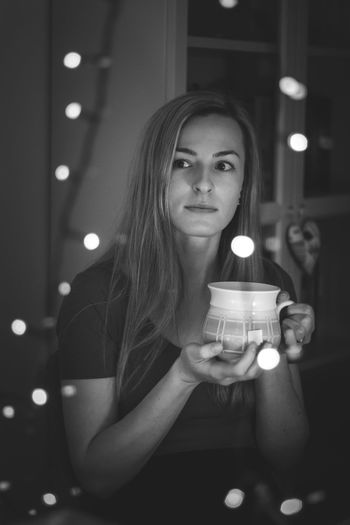 Portrait of young woman with illuminated candles