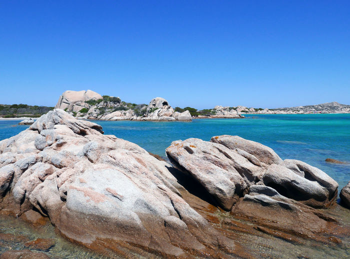 Scenic view of rocks by sea against clear blue sky