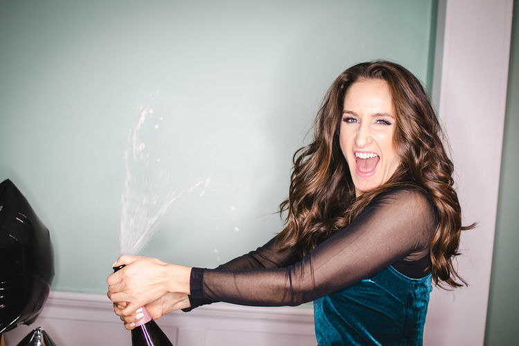 Portrait Of Woman Spraying Champagne Against Wall