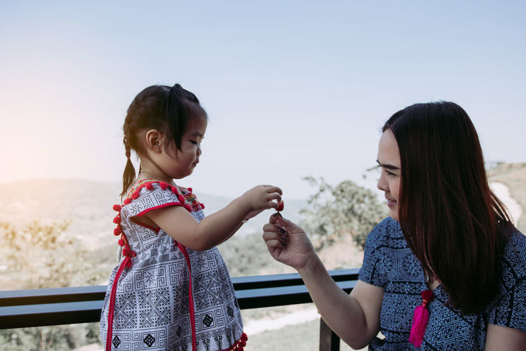Smiling mother giving strawberry to cute daughter against clear sky