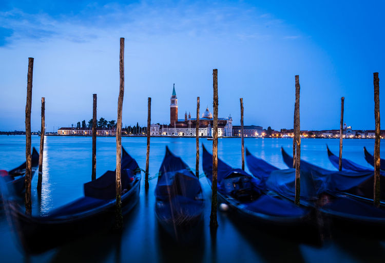Gondolas moored by wooden post at harbor against sky at dusk
