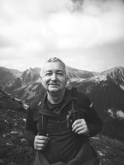 Portrait of smiling man standing on mountain