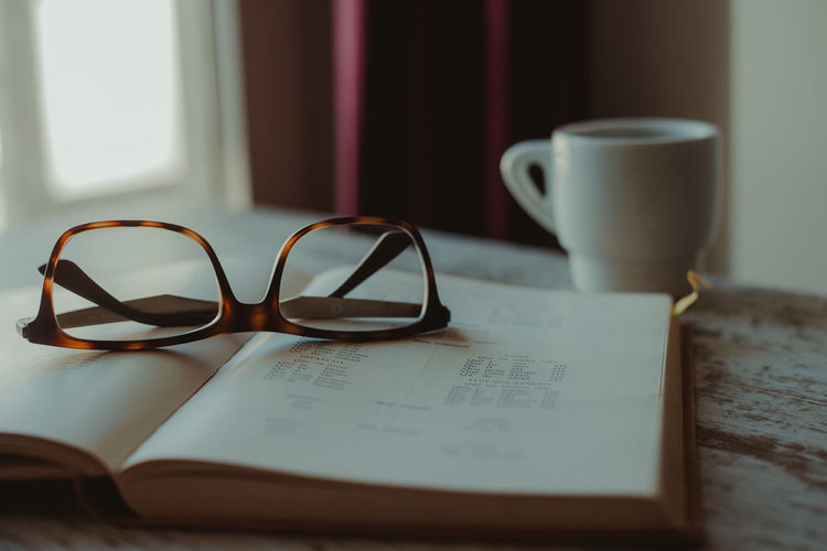 Eyeglasses  Education Learning Studying Coffee Time Coffee Drink Open Personal Accessory Eyewear Communication Food And Drink Selective Focus Coffee Cup No People Mug Close-up Indoors  Eyeglasses  Publication Still Life Book Table Glasses Paper Cup