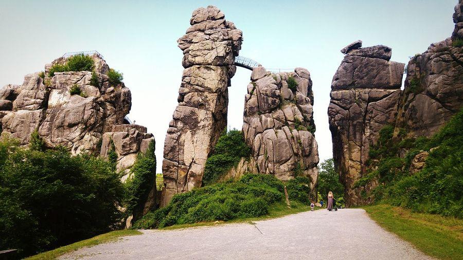 Rear view of man walking on rock formation