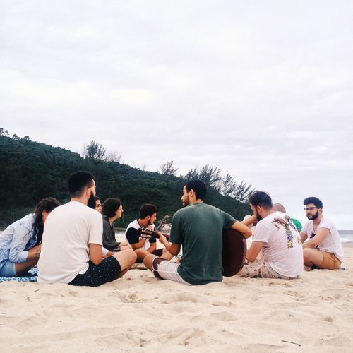 People playing guitar at beach against sky