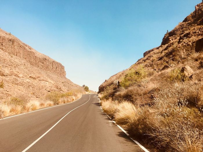 Road on Gran Canaria island in Spain Mountain Road Travelling Sunny Day Ahead Beauty In Nature Scenery Day Mountain Outdoors Clear Sky Asphalt Dividing Line No People Nature Sunlight Scenics Winding Road Plant Landscape White Line