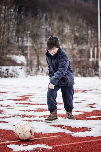 boy kick the ball on sports field in the winter season Football Frozen Ice Snow ❄ Sports Field Winter Beginning Boy Childhood Cold Temperature Kid Leisure Activity Nature Playing Playing Field Red Place Snow Sport Sports Ground Start Winter