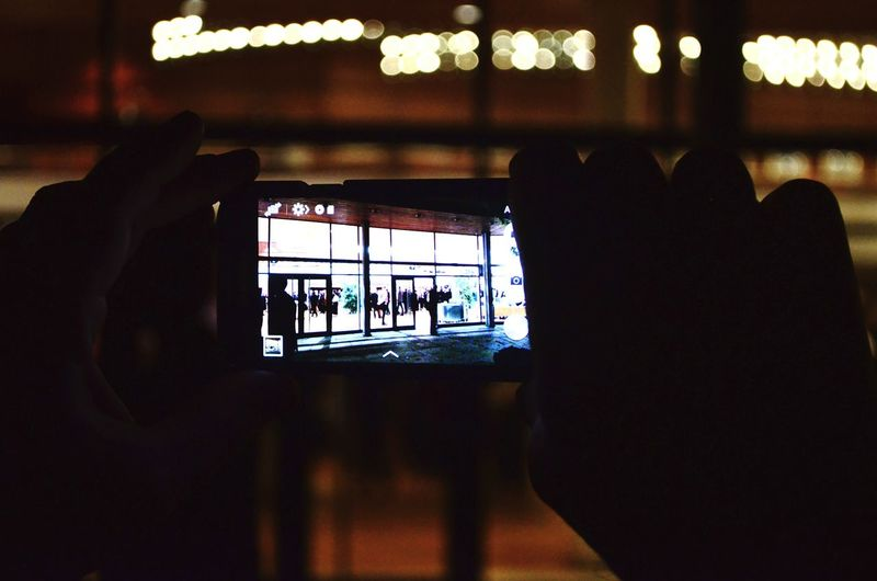 Close-up of silhouette people photographing in nightclub