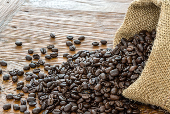 Spilled coffee beans Black Brown Burlap Sack Close-up Coffee Coffee Bean Dark Day Food And Drink Freshness Gunny Indoors  Large Group Of Objects No People Sack Seed Table