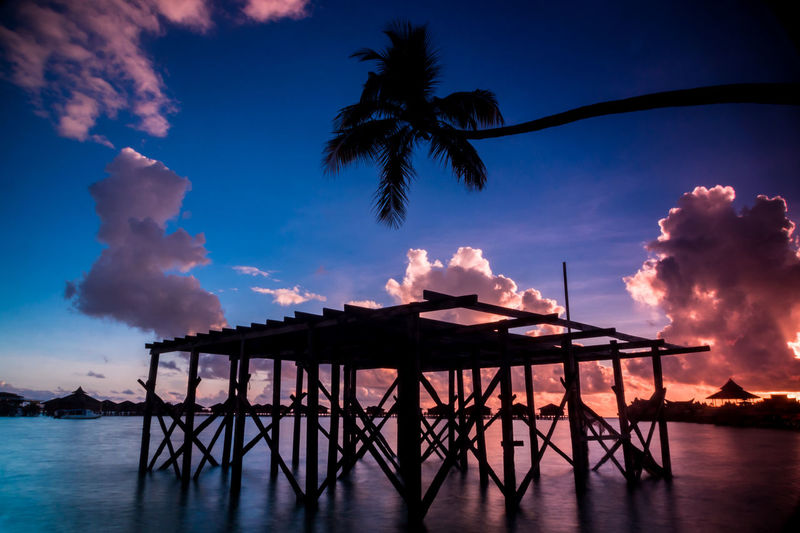 Silhouette of coconut tree at sunrise Beauty In Nature Calm Cloud Cloud - Sky Cloudy Day Gazebo Idyllic Jetty Nature No People Non-urban Scene Outdoors Pier Scenics Silhouette Sky Sunset The Great Outdoors - 2016 EyeEm Awards The Great Outdoors With Adobe Tranquil Scene Tranquility Water Weather Wood - Material