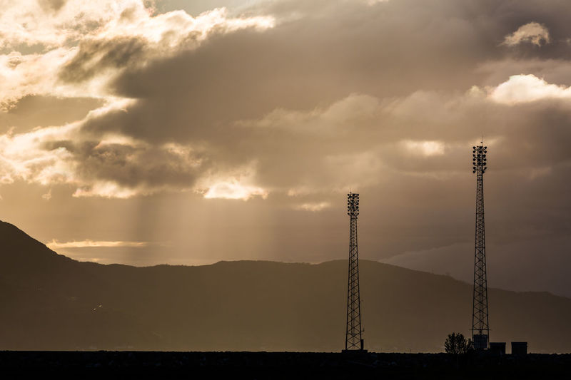 Scenic View Of Communication Towers And Mountains Against Cloudy Sky