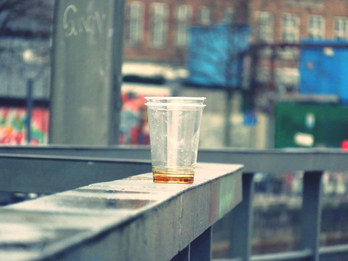 Leftover alcohol in disposable cup on wet railing