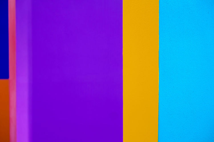 Abstract geometric pattern on concrete wall Art And Craft Backgrounds Blue Built Structure Choice Close-up Copy Space Day Flag Full Frame Indoors  Multi Colored No People Pattern Pink Color Purple Striped Variation Vibrant Color Wall - Building Feature Yellow