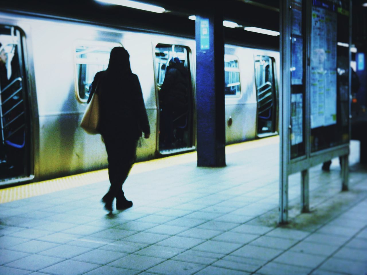 real people, public transportation, rear view, transportation, railroad station, railroad station platform, one person, full length, women, lifestyles, train - vehicle, men, standing, mode of transport, rail transportation, illuminated, outdoors, day, adult, people