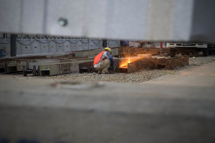 Worker welding metal at construction site