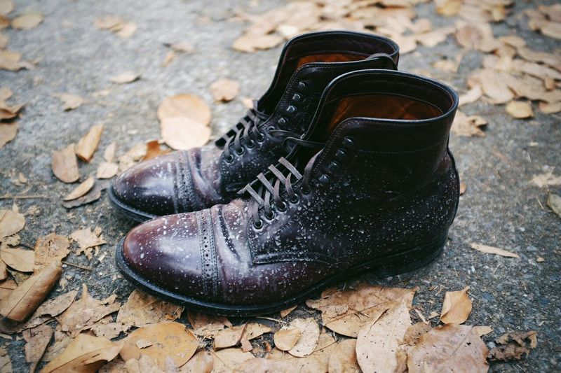 Close-up of boots by autumn leaves on road
