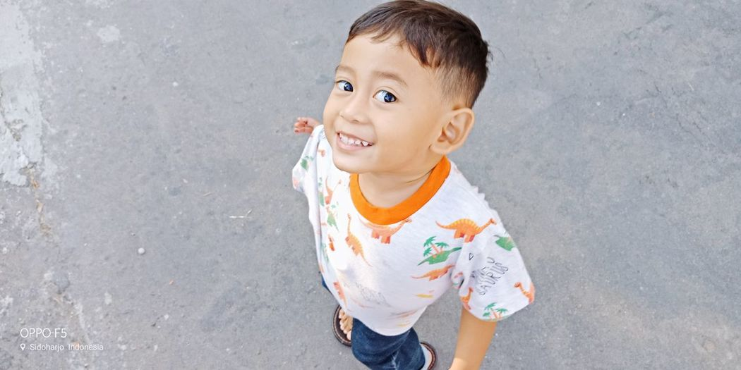 High angle portrait of cute boy standing on street