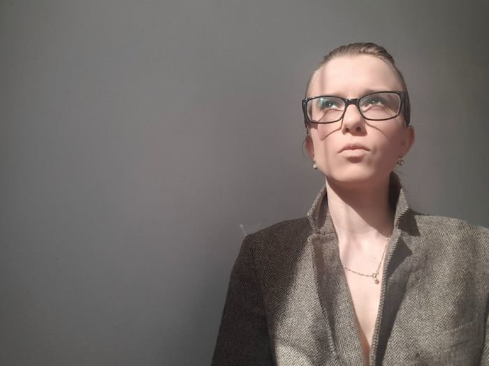 Close-up of businesswoman wearing eyeglasses looking up against wall