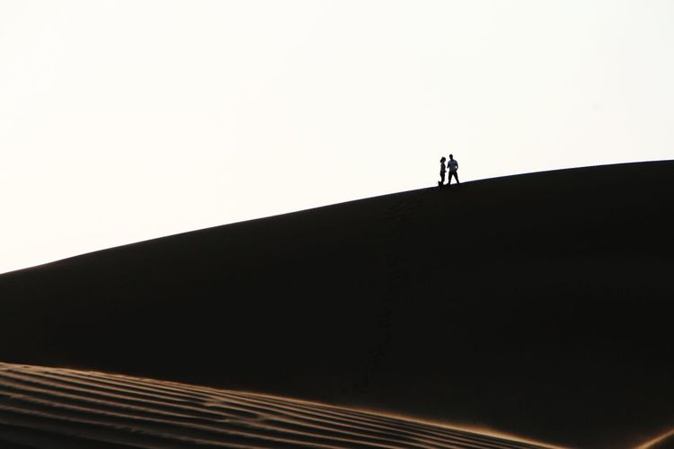 Low angle view of silhouette man standing by building against clear sky