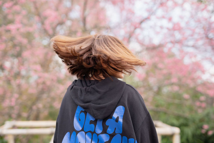 Rear view of woman shaking head in park
