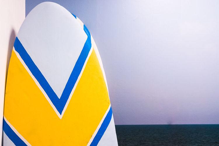 Close-up of yellow arrow symbol on beach