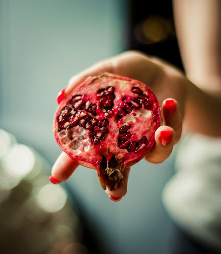 Cropped Hand Of Woman Holding Pomegranate
