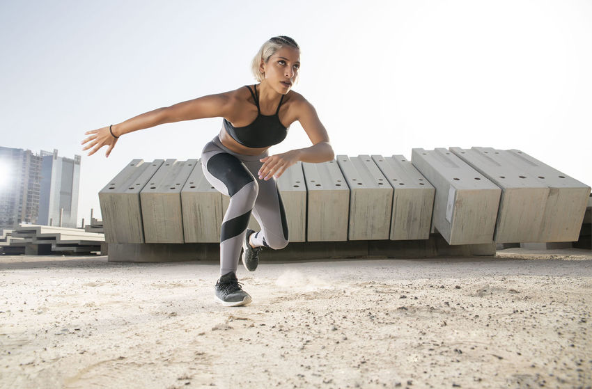 Middle Eastern Girl with short braided hair exercising on a dusty construction site wearing gray and black fitness outfit on a hot bright sunny day. Exercising Jumping Off Rocks Sitting Beautiful Woman Bright Day Casual Clothing Clothing Day Dusty Effort Fitness Model Front View Full Length Hot Day ☀ Leisure Activity Lifestyles Looking At Camera Middle Eastern Woman Nature One Person Outdoors Portrait Real People Sitting Sky Sports Clothing Stretching Women Young Adult Young Women