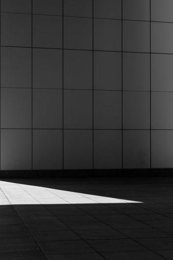 Shadow on tiled floor against wall