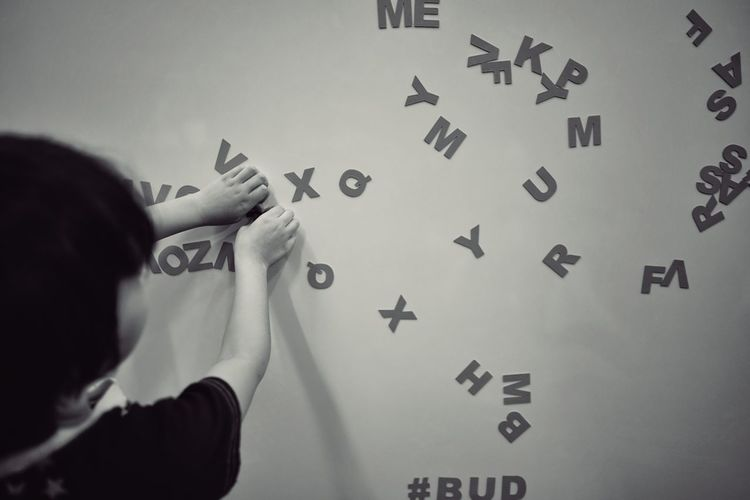 Girl playing with alphabets against wall