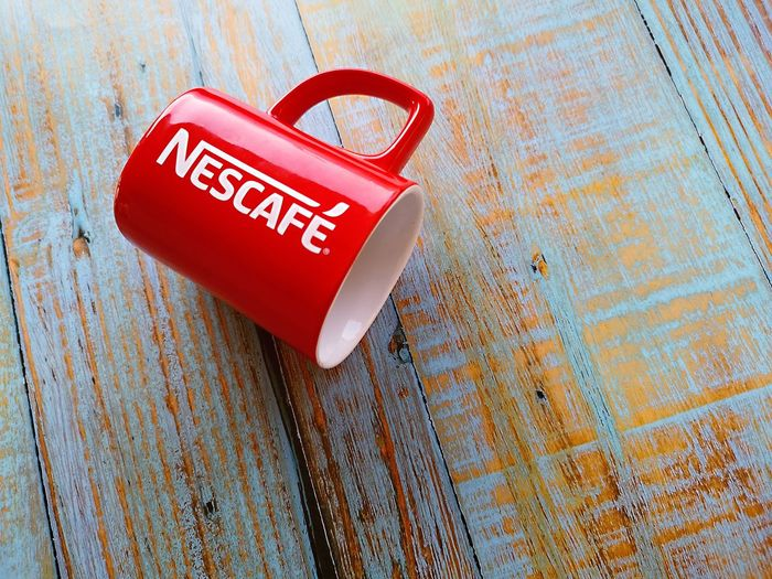 Nescafe mug over blue wooden background with selective focus. Selective Focus Object Mug Red Colors Red Wood - Material Text Single Object Close-up Information