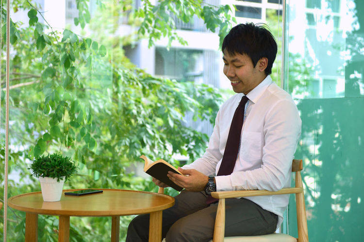 Businessman reading book at table in office