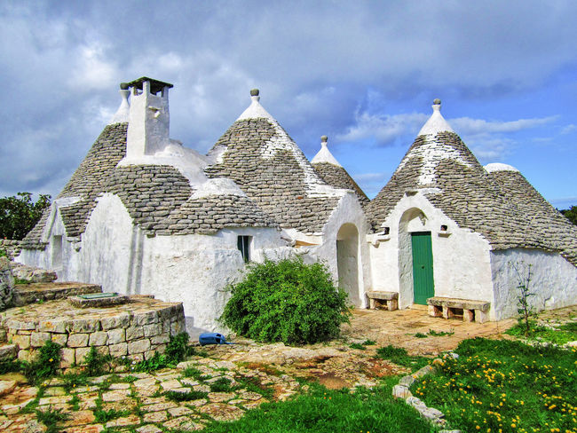 Group of Trulli, traditional old houses and old stone wall under blue sky in countryside, Puglia, Italy Alberobello Ancient Mediterranean  Puglia Roof Wall Architecture Building Exterior Built Structure History Italy Landscape Old Old Houses Outdoor Outdoors Salento Spirituality Spring Stone Summer Truck Trullo Valle D'itria Wall Stone