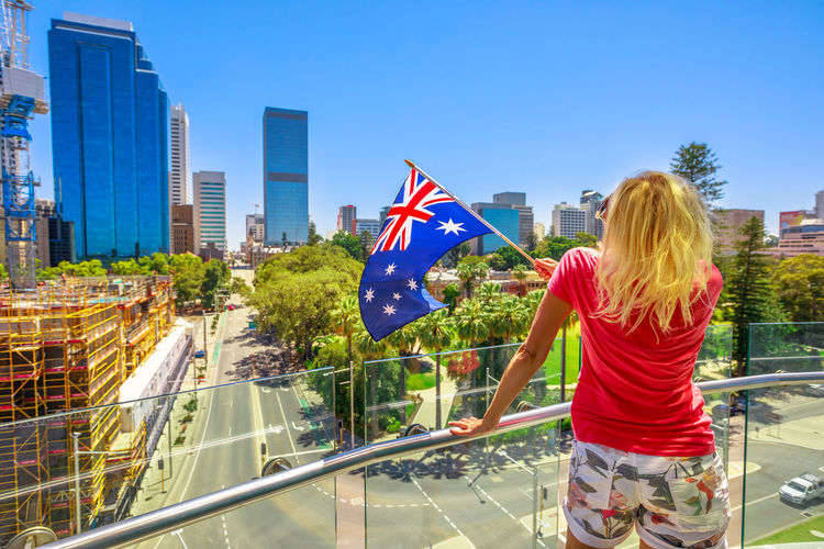 Rear view of woman with australian flag standing at building balcony in city