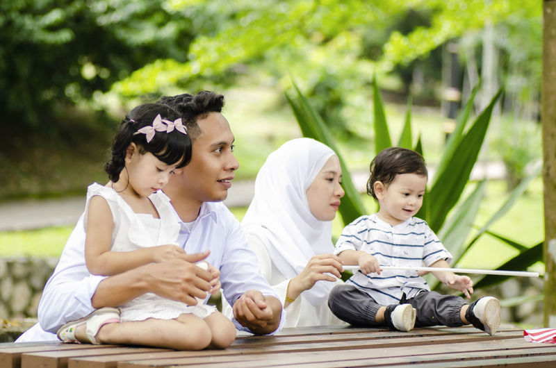 young father and mother spending time with their children at park during weekend Child Childhood Group Of People Men Sitting Males  Boys Family Parent Leisure Activity Women Real People Mother Lifestyles Togetherness Adult Casual Clothing Girls Females Son Innocence Outdoors Daughter