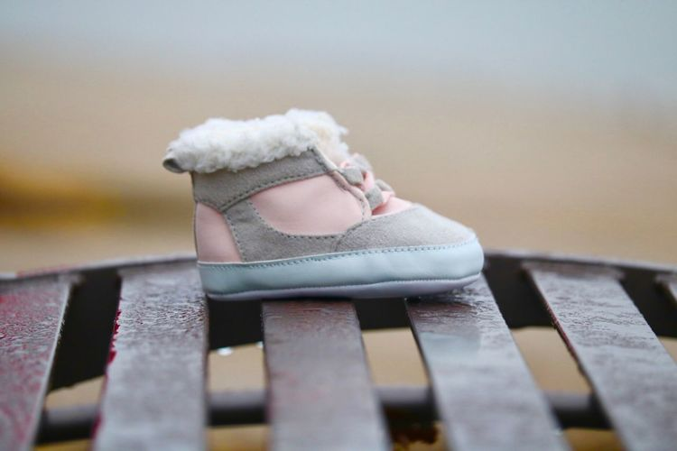 Close-up of baby booties on metal