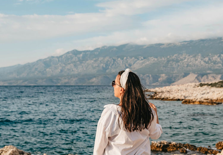 Woman looking at sea against mountain
