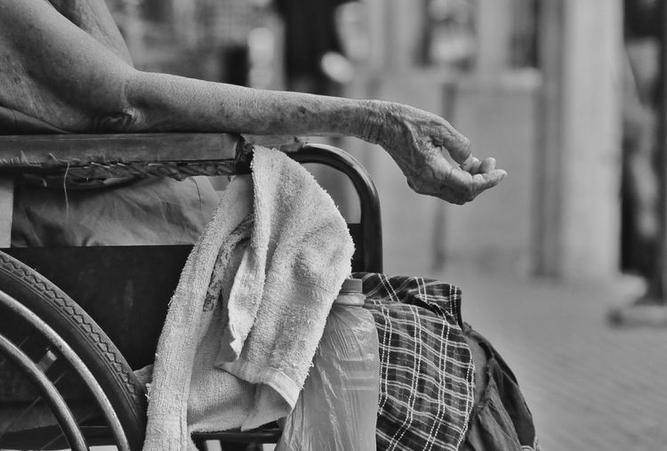 Midsection Of Female Beggar On Wheelchair At Street