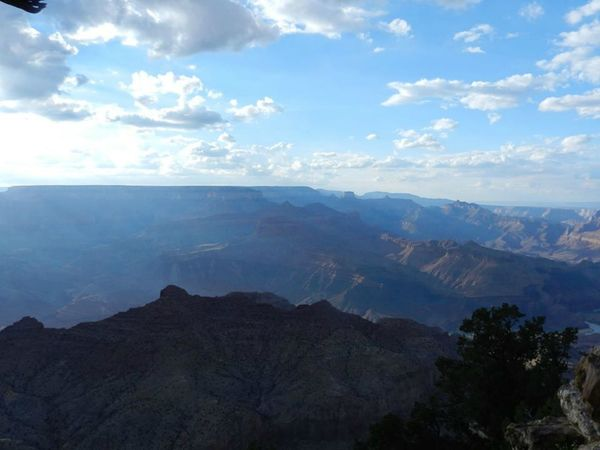 Smokey View of the Grand Canyon Arizona Beauty In Nature Cloud Cloud - Sky Cloudy Day Geology Grand Canyon Idyllic Landscape Majestic Mountain Mountain Range Nature Outdoors Physical Geography Remote Rock Formation Scenics Sky Sun Rays Tourism Tranquil Scene Tranquility Travel Destinations