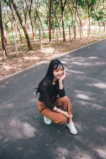 High angle view of thoughtful young woman crouching on road against trees in forest