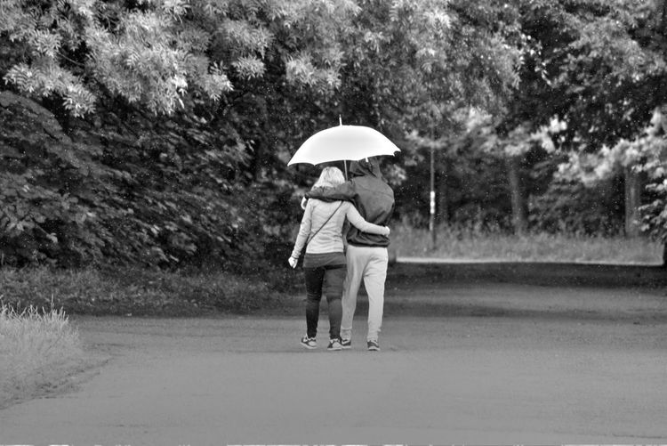 Rear view of couple with umbrella walking on road against trees during monsoon