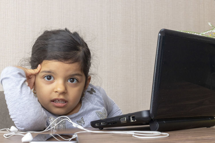 Cute girl using laptop while sitting on table at home