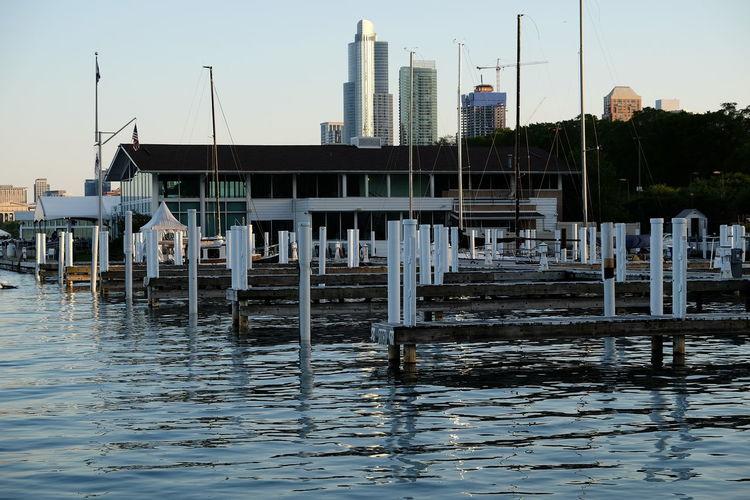 Pier on lake against buildings in city