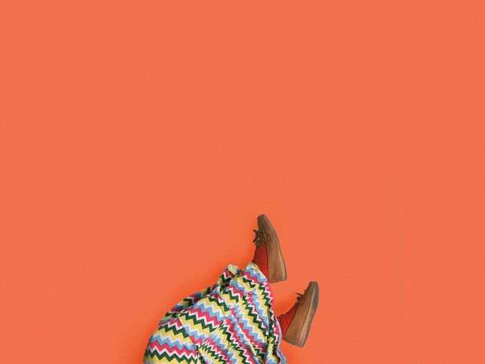Low Section Of Woman Wearing Shoes Against Orange Background