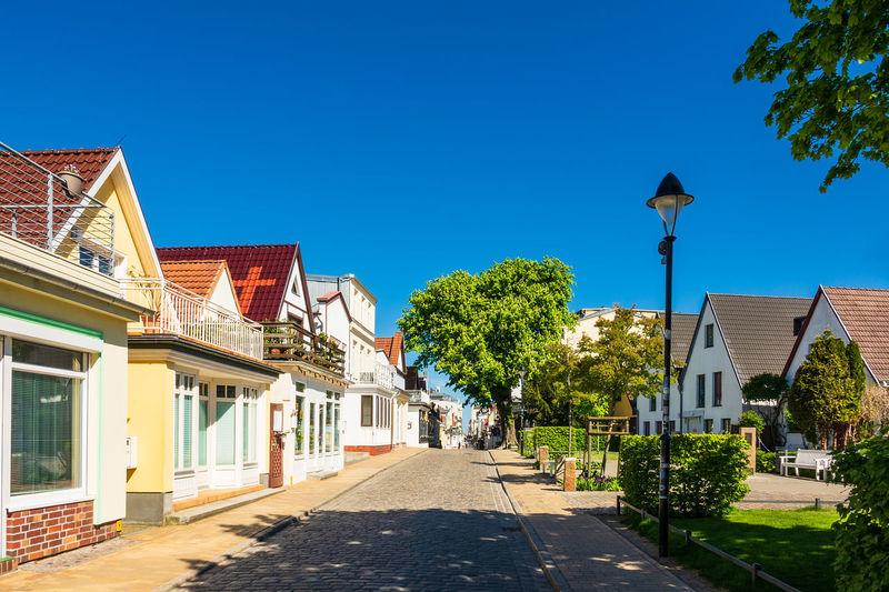 Street Amidst Houses And Trees Against Clear Blue Sky